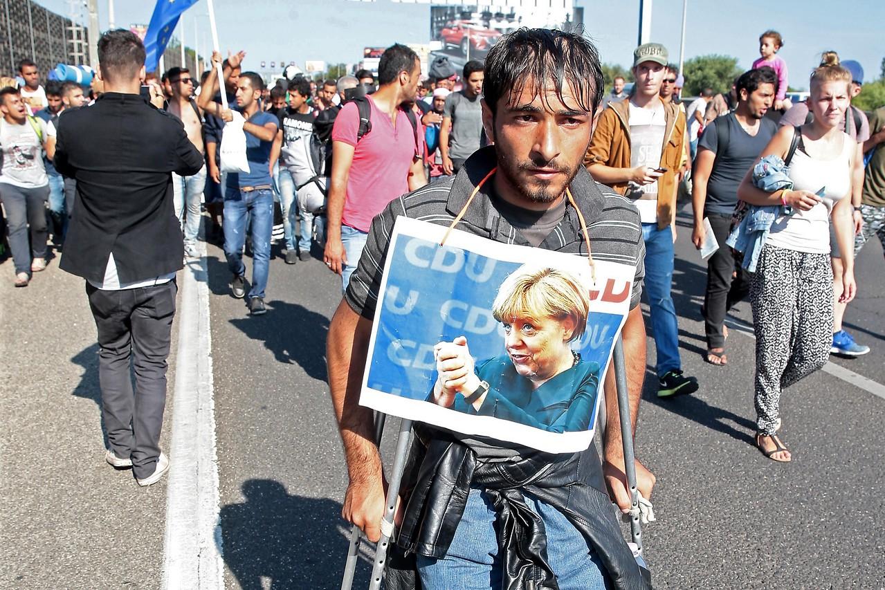 Flüchtling auf Krüken mit umgehängten Bild der deutschen Kanzlerin Markel am 4. September 2015