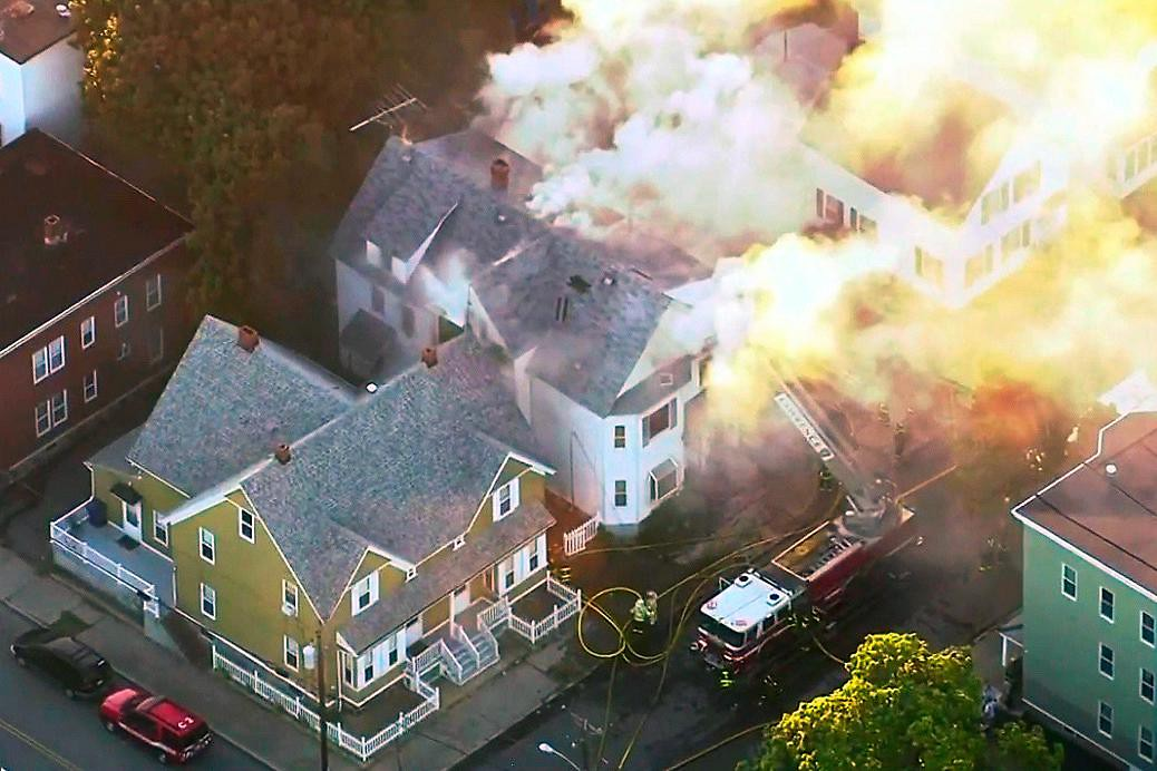 Luftaufnahme eines Hauses, aus dem Flammen und Rauch steigen