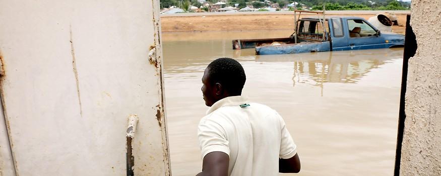 Mann vor überflutetem Haus in Nigeria