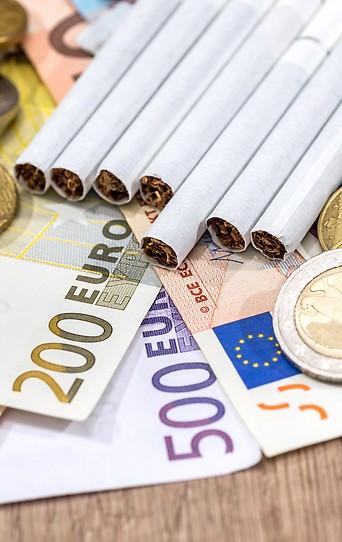 Zigaretten liegen auf Geldscheinen und Münzen