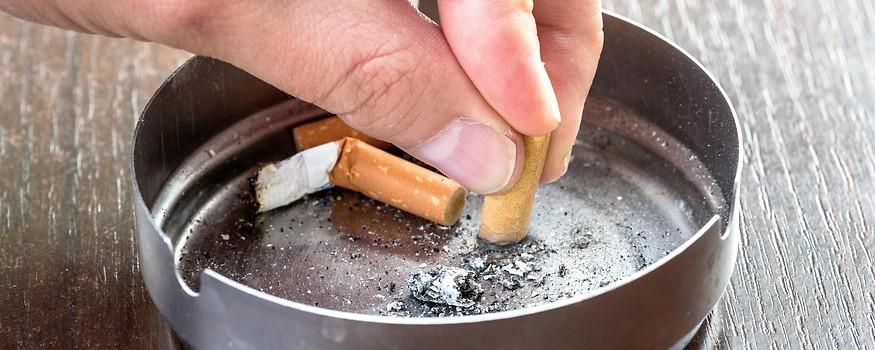 Person dämpft eine Zigarette in einem Aschenbecher aus