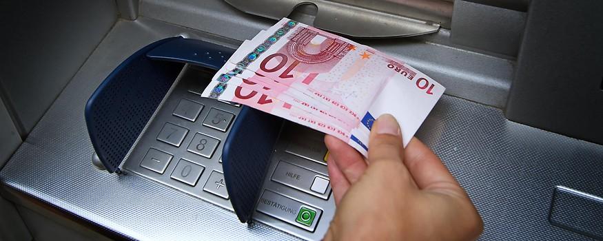 Eine Person hebt bei einem Bankomaten Geld ab