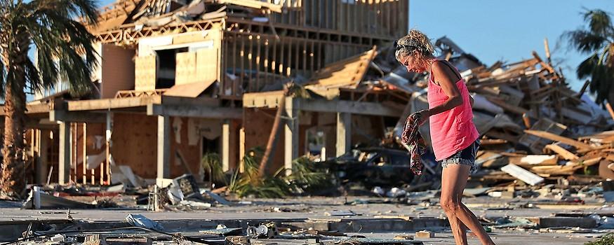 Eine Frau vor einem zerstörten Haus