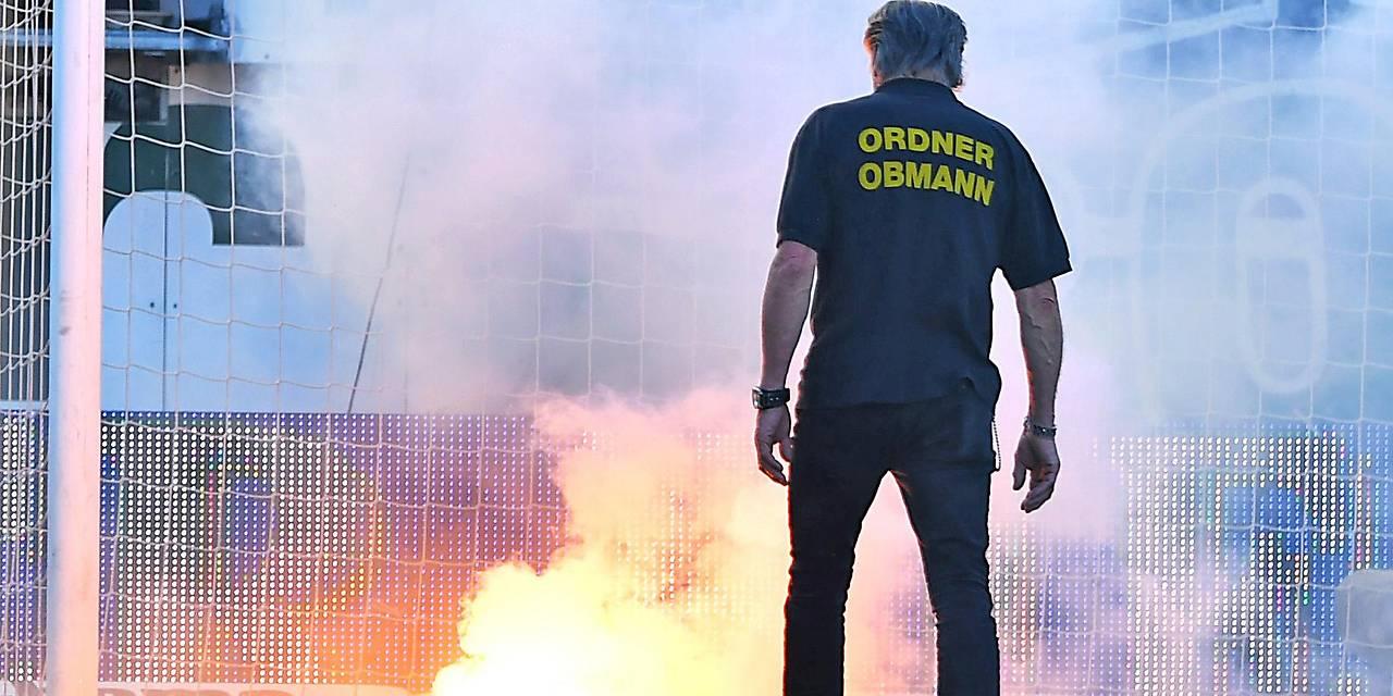 Ein Ordner steht vor einem bengalischen Feuer auf dem Spielfeld
