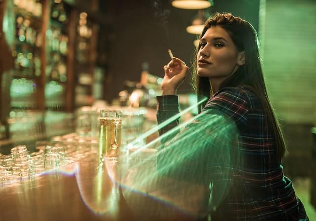 Junge Frau sitzt mit einer Zigarette in einer Bar