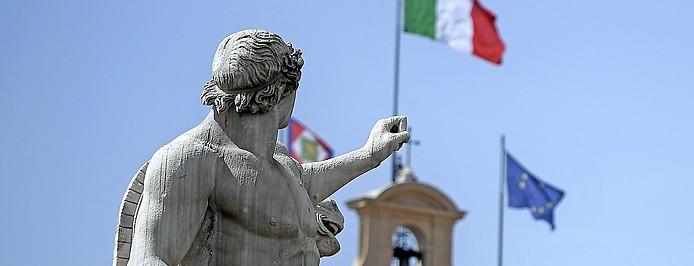 Statue auf dem Quirinalpalast in Rom neben italiensischer und EU-Flagge