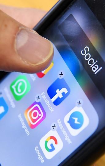 Ein Mann hält ein Smartphone, auf dem Apps zu Sozialen Medien zu sehen sind