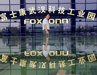 A man walks past a logo of a Foxconn factory in Wuhan (China)