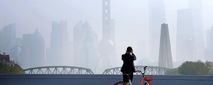 Mann fotografiert die im Smog versinkende Skyline von Schanghai