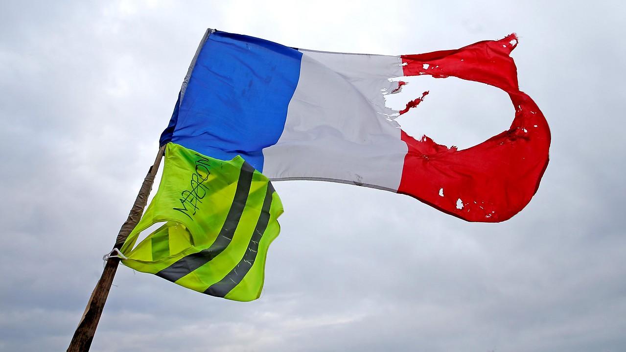 Eine zerstörte französische Flagge und eine gelbe Weste