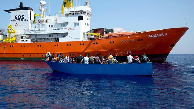 """Flüchtlinge in einem kleinen Boot vor dem Rettungsschiff """"Aquarius"""""""
