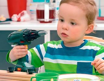 Bub mit einer Spielzeugbohrmaschine