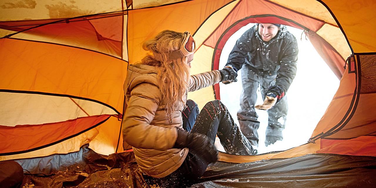 Ein Mann hilft einer Frau in Winterkleidung aus einem Zelt
