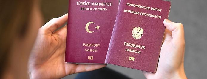 Person hält einen türkischen und österreichischen Reisepass in den Händen