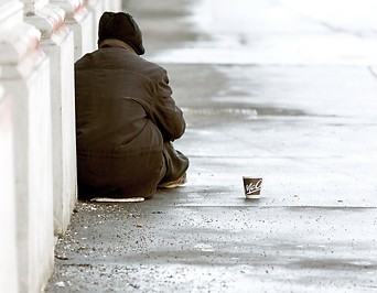 Obdachloser sitzt auf einem Gehsteig in Wien