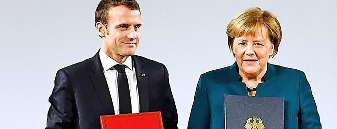 Frankreichs Präsident Emmanuel Macron und die deutsche Bundeskanzlerin Angela Merkel halten das Abkommen
