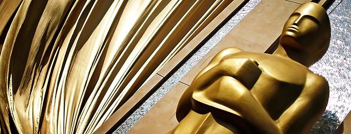Oscar-Statue neben einem goldenen Vorhang