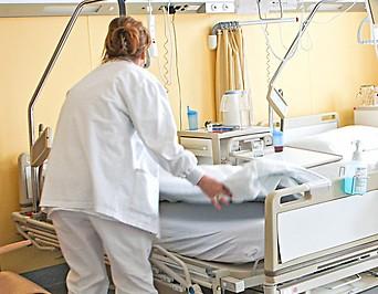 Eine Frau überzieht ein Bett in einem Krankenhaus