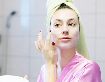 Frau schmiert sich Creme ins Gesicht