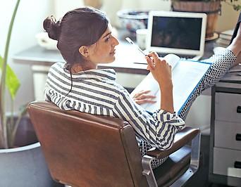 Eine Frau sitzt mit Unterlagen an einem Schreibtisch