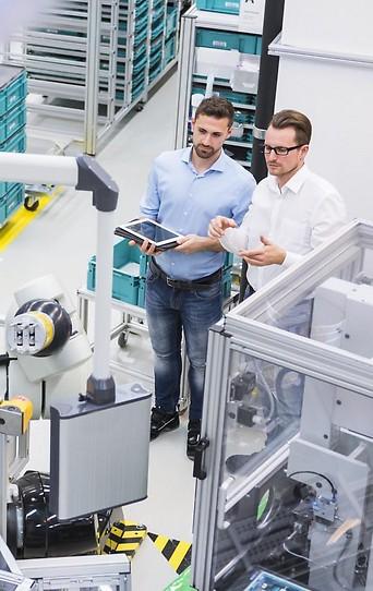Zwei Männer mit einem Tablet in einer Fabrik