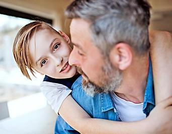 Ein Bub umarmt seinen grauhaarigen Vater
