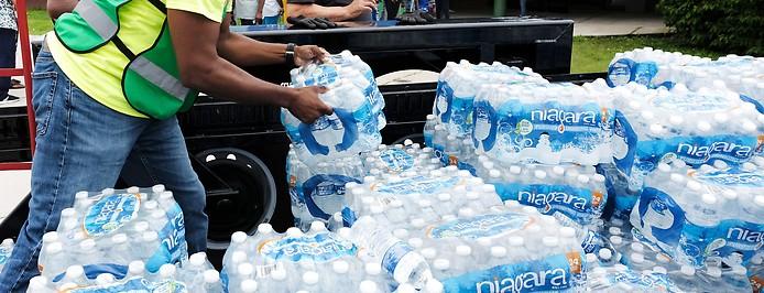 Mann verteilt Wasserflaschen