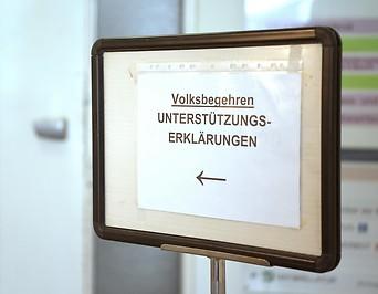 Ein Schild weist den Weg zu einem Volksbegehren
