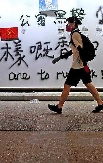 Protestteilnehmer mit Mundschutz passiert eine mit Graffiti beschmierte Wand in Hongkong