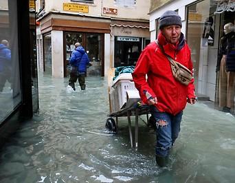Mann geht mit vollgepacktem Schubkarren durch Hochwasser