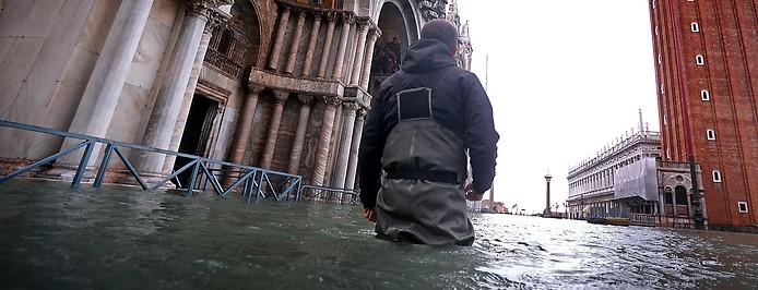 Mann in Hochwasserhosen steht bis zu den Oberschenkeln am Markusplatz in Venedig im Wasser