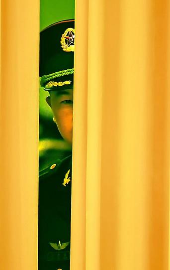 Chinesischer Soldat blickt durch eine Vorhangspalte