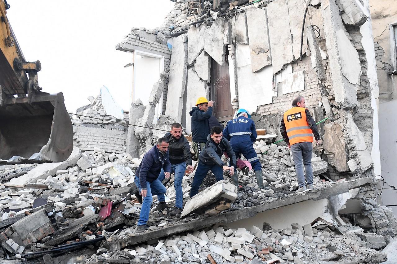 Helfer auf einem zerstörten Gebäude