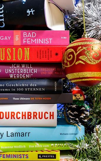 Eine Auswahl von Sachbüchern liegt auf weihnachtlichem Christbaumschmuck