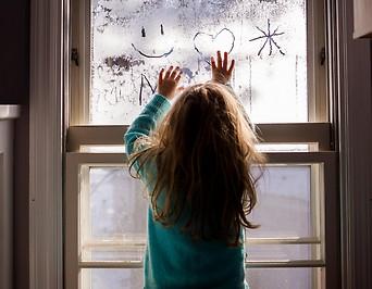 Ein Kind zeichnet auf einem Fenster Figuren