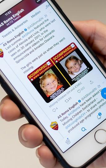 Frau hält Handy mit dem Twitter-Acount des AS Roma mit einer Anzeige für vermisste Kinder