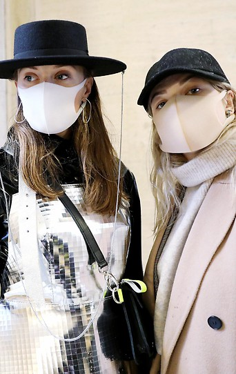 """Gerda Liudvinaviciute, Ingrida Jasinske, and Ruta Petrauskaite, präsentieren Schutzmasken und Kleidung von """"kARTu"""" während einer Modenschau auf der London Fashion Week"""