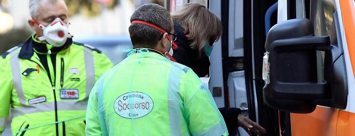 Frau mit Mundschutz steigt in in Casalpusterlengo in einen Rettungseinsatzwagen, neben ihr Sanitäter ebenso mit Mundschutz