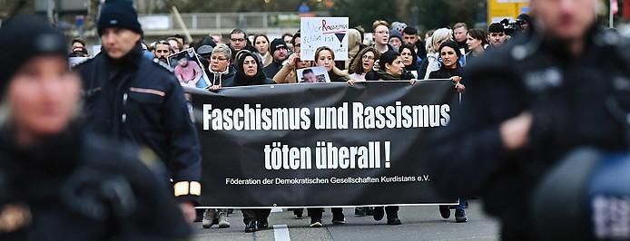 Zahlreiche Menschen gehen bei einem Trauermarsch vom Tatort Heumarkt zum Tatort Kurt-Schumacher-Platz und halten dabei Transparente und Fotos der Opfer in den Händen