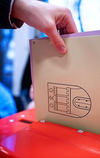 Person wirft Stimmzettel in die Wahlurne