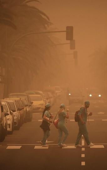 Menschen in Karnevalskostümen in Teneriffa während einem Sandsturm