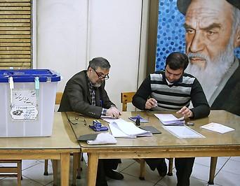 Wahlbeisitzer sortieren Stimmzettel neben leeren Wahlurnen
