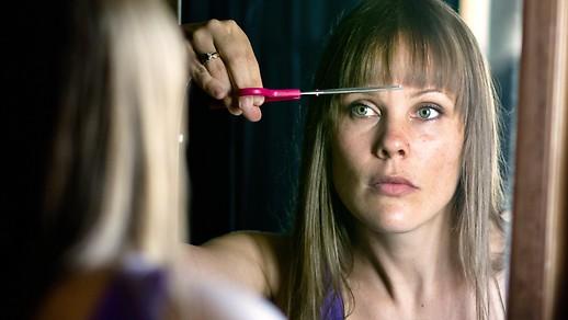 Frau schneidet ihre Haare selbst