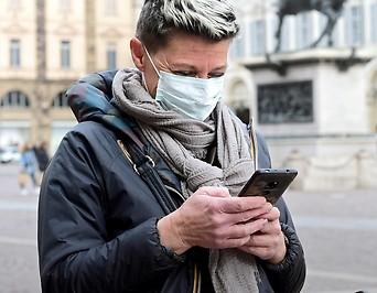 Frau mit Gesichtsmaske blickt auf ein Handy