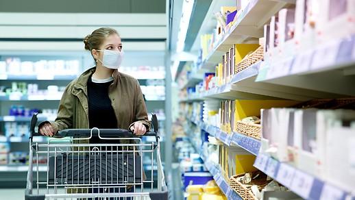 Frau mit Schutzmaske beim Einkauf in einem Supermarkt