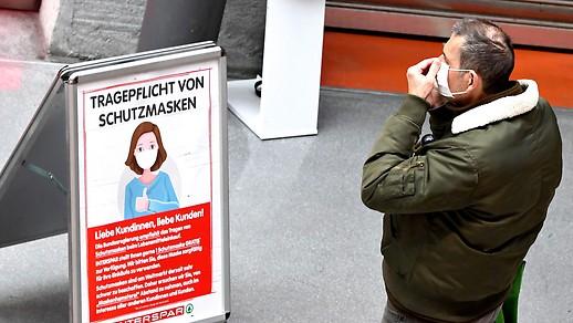 Ein Mann beim Anlegen einer Schutzmaske vor einem Lebensmittelgeschäft in Wien