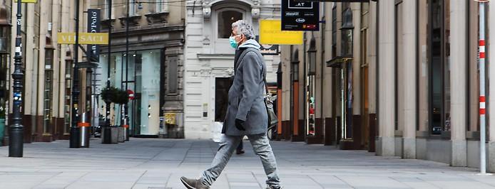 Mann überquert den Wiener Graben mit Maske