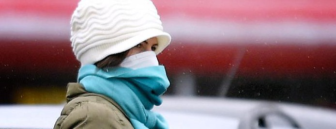 Frau mit Schutzmaske trägt ihren Einkauf