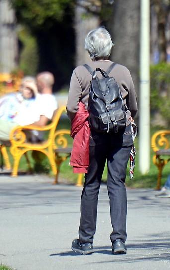 Eine ältere Frau spaziert in einem Park an besetzten Parkbänken vorbei