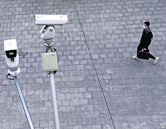 Ein Mann mit Schutzmaske geht an Überwachungskameras vorbei